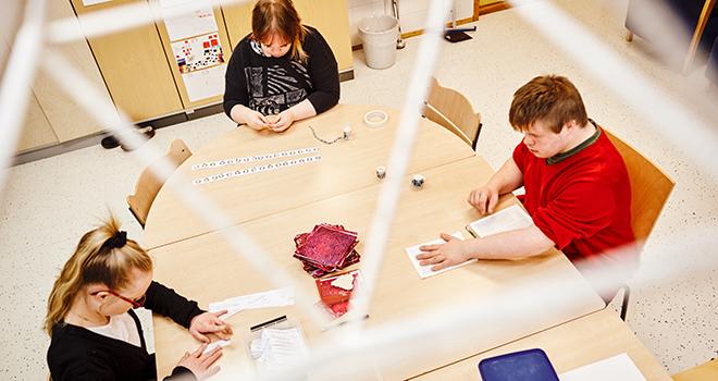 Ammattiopisto Spesia kuva luokasta, 3 oppilasta tekee pöydän ääressä tehtäviä.